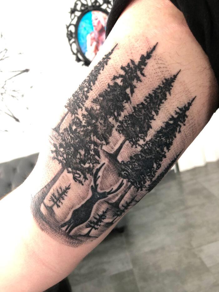 Tatuaje realista de bosque con ciervo