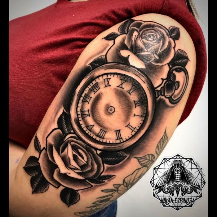 Tatuaje de un reloj con rosas en el hombro